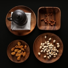 Wooden continental breakfast bread thickened circular disc plate of small fruit seeds nuts snacks dry cakes dishes